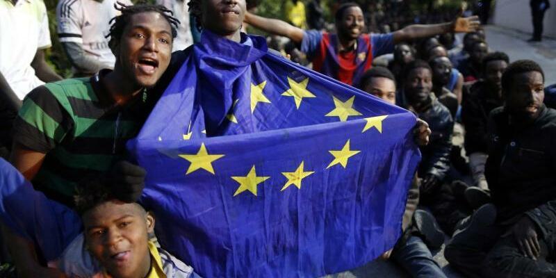 Ceuta - Foto: Flüchtlinge sitzen in der spanischen Exklave Ceuta in Marokko mit einer EU-Flagge in den Händen auf dem Boden. Foto:Jesus Moron