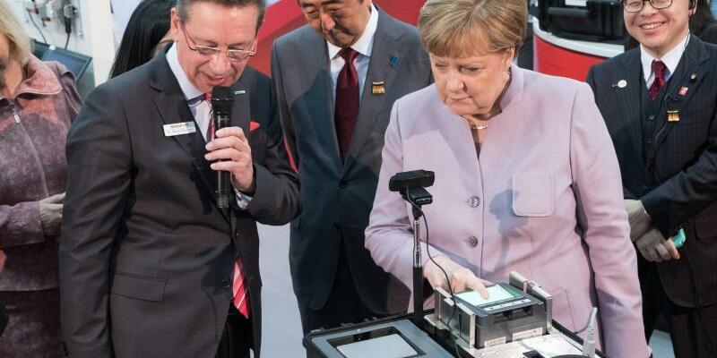 CeBIT-Eröffnungsrundgang - Foto: Ganz entspannt bei der CeBIT:Rainer Baumgart, Vorstand der secunet Security Networks AG, der japanische Premierminister Shinzo Abe und Bundeskanzlerin Angela Merkel beim Eröffnungsrundgang. Foto:PeterSteffen