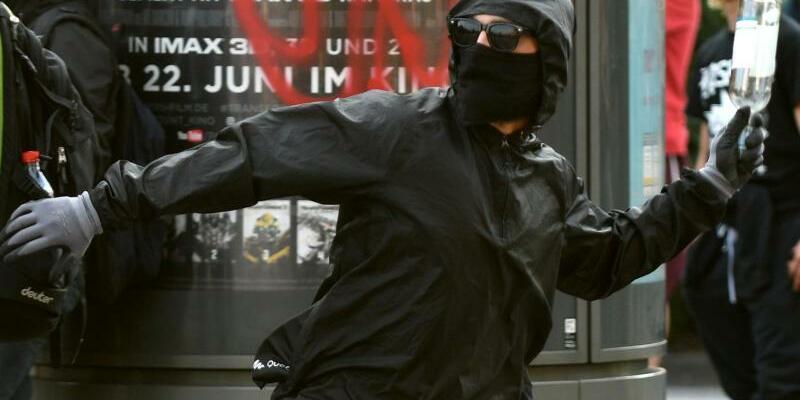 G20-Gipfel - Foto: Ein maskierter Demonstrant wirft eine Flasche auf Polizeikräfte inHamburg. Die Union fordert eine «europäische Extremistendatei für Linksradikale». Foto:Axel Heimken