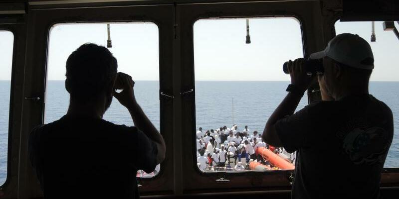 Rettungseinsätze im Mittelmeer - Foto: Kapitän und Offizier des Rettungsschiffs «Aquarius» blicken auf das Mittelmeer. An Deck des Schiffs sind bereits Migranten zu sehen, die zuvor an Bord von Einsatzkräften der Hilfsorganisationen Ärzte ohne Grenzen und SOSMediterranee gerettet wurden. Foto