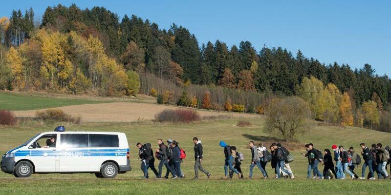 Flüchtlinge - Foto: Flüchtlinge gehen im November 2015 nahe Wegscheid in Oberbayern nach der Überquerung der Grenze hinter einem Polizeifahrzeug zu einer Aufnahmestation. Für CSU-Chef Horst Seehofer ist eine Flüchtlingsobergrenze keine Bedingung mehr für eine Regierungskoali