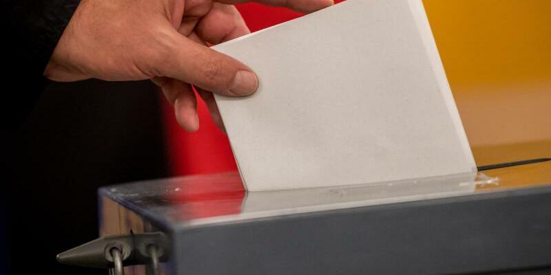 Wähler wirft Stimmzettel in Wahlurne - Foto: Michael Kappeler