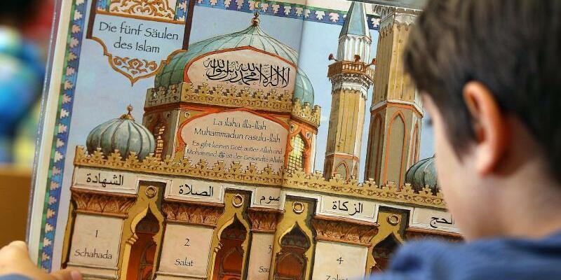 Islamunterricht - Foto: Ein Junge liest in Bonn während des islamischen Religionsunterrichts in einem Schulbuch. Foto:Oliver Berg/Archiv
