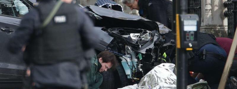 London - Foto: Polizisten untersuchen in der Nähe des Londoner Parlaments ein Auto, mit dem mehrere Menschen überfahren worden sein sollen. Foto:Yui Mok