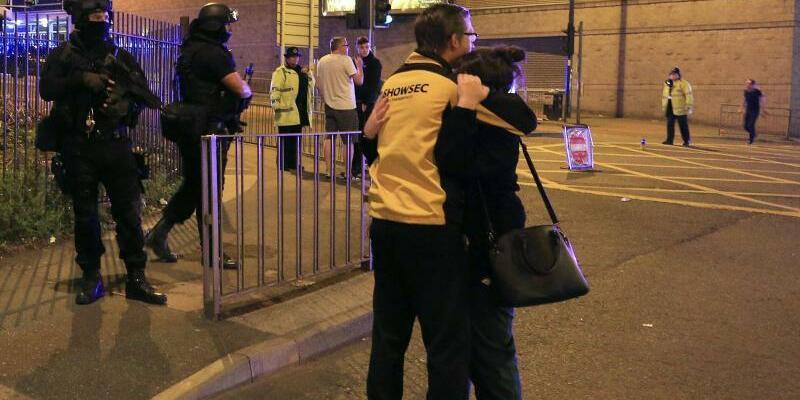 Manchester - Foto: Überlebende liegen sich in den Armen, während Einheiten der Polizei in der Nähe der Manchester Arena im Einsatz sind. Foto:Peter Byrne