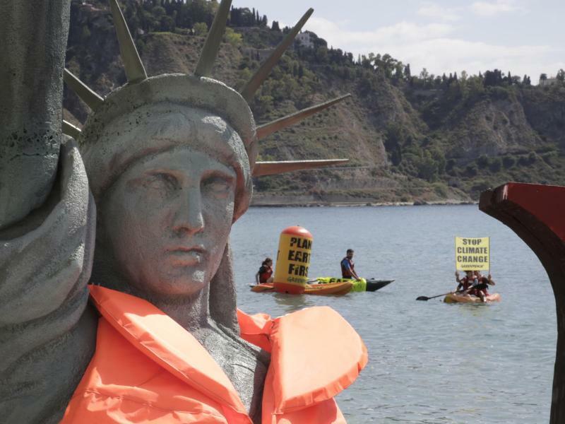 Protest - Foto: Greenpeace-Aktivisten während einer Protestaktion hinter einer Nachbildung einer Freiheitsstatue mit Schwimmweste am Strand von Taormina auf Sizilien. Foto:Tommaso Galli/Greenpeace Italien
