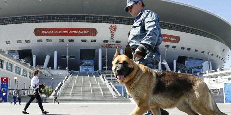 Confederations Cup - Foto: Sicherheit wird in Russland groß geschrieben: Ein Wachmann mit Hund läuft vor dem Stadion in St. Petersburg entlang. Foto:Kyodo
