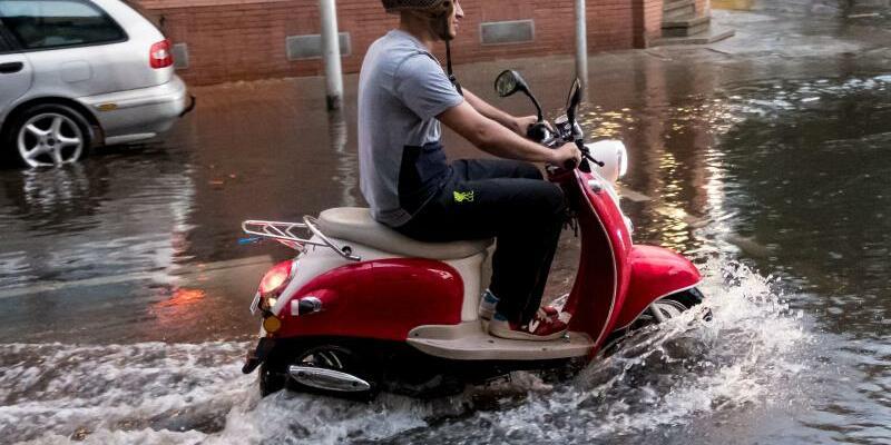 Unwetter in Hannover - Foto: Mit Bugwelle:Ein Rollerfahrer bahnt sich seinen Weg durch einen übefluteten Stadtteil in Hannover. Foto:PeterSteffen