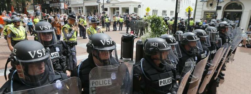 Unfallort - Foto: Polizisten sperren den Unfallort ab, an dem ein Auto in eine Gruppe von Gegendemonstranten gefahren war. Foto:Steve Helber