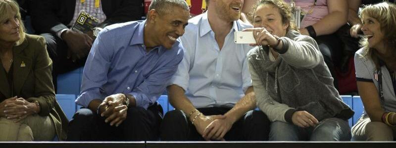 Barack Obama und Prinz Harry - Foto: Eine Besucherin fotografiert sich mit dem ehemaligen US-Präsidenten (2.v.l.). Foto:Chris Donovan