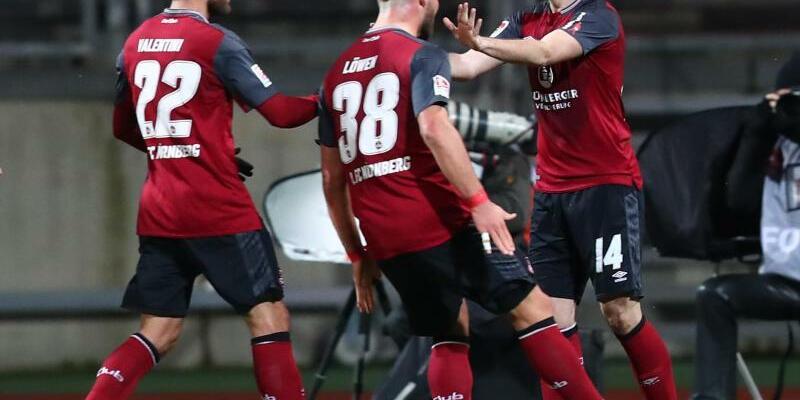 1. FC Nürnberg - Erzgebirge Aue - Foto: Club-Doppeltorschütze Kevin Möhwald (r) wird von seinen Teamkollegen gefeiert. Foto:Daniel Karmann