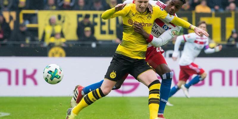 Rückkehrer - Foto: BVB-Rückkehrer Marco Reus (l) behauptet sich beim Kampf um den Ball gehen Gideon Jung vom HSV. Foto:Guido Kirchner