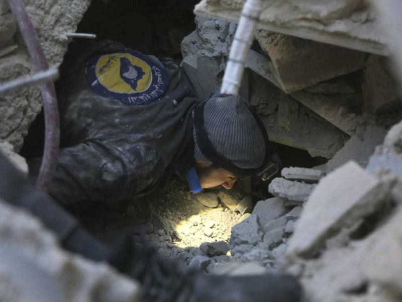 Luftangriffe in Ost-Ghuta - Foto: Ein Mann sucht in den Trümmern eines während des Angriffs durch die syrische Luftwaffe zerstörten Hauses nach Überlebenden. Foto:Syrian Civil Defense White Helmets/AP
