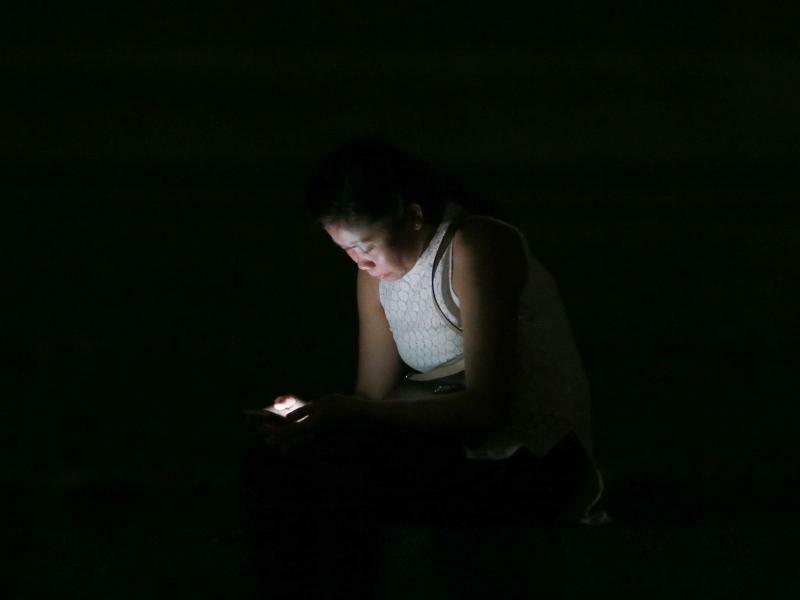 Earth Hour auf den Philippinen - Foto: Rund um den Globus gehen während der «Earth Hour» für eine Stunde alle Lichter aus - oder zumindest fast alle: Auf den Philippinen spendet ein Smartphone seiner Besitzerin Licht. Foto:Bullit Marquez/AP