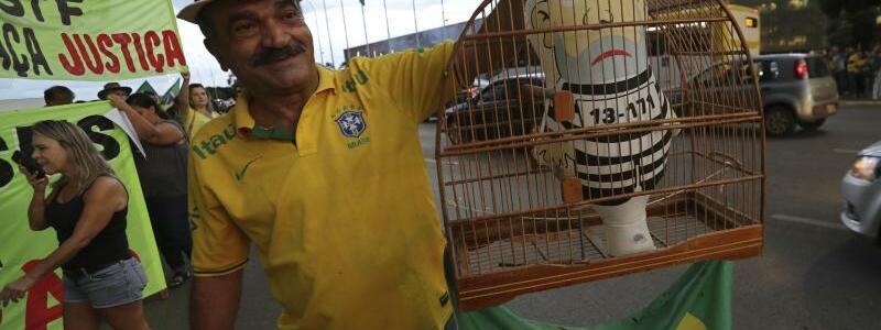Hinter Gittern - Foto: Hinter Gittern: Ein Demonstrant hält einen Vogelkäfig mit einer Puppe in Form des ehemaligen Präsidenten Lula da Silva in Gefängnismontur. Foto:Eraldo Peres/AP