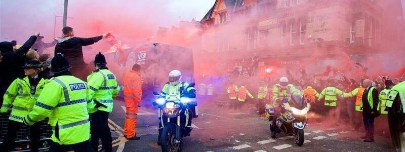 Anfahrt - Foto: Die Mannschaftsbusse der beiden Teams mussten in Liverpool durch eine Gasse von bengalische Feuer abbrennende Fans von der Polizei zum Stadion geleitet werden. Foto:XinHua