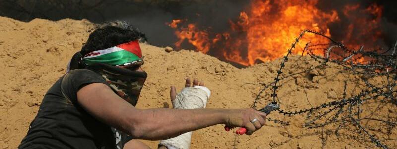 Israelische Grenze - Foto: Ein palästinensischer Demonstrant versucht, eine Barriere aus Stacheldraht durchzuschneiden. Foto:Ashraf Amra/APA Images via ZUMA Wire