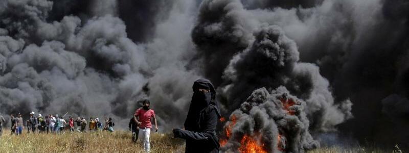 Schwarze Wand - Foto: Verschleierte Palästinenserin bei den Zusammenstößen. Die radikalislamische Hamas hatte vor einer Woche den «Marsch der Rückkehr» gestartet, insgesamt sollen die Proteste sechs Wochen andauern. Anlass ist der 70. Jahrestag der Gründung Israels. Foto:Moha