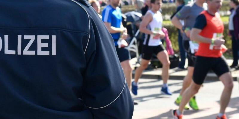 Berliner Halbmarathon - Foto: Berliner Halbmarathon:Ein Polizeibeamter steht an der Laufstrecke. Foto:Paul Zinken