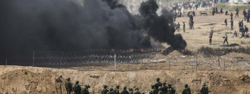 Grenzzaun - Foto: Konfrontation:IsraelischeSoldaten nehmen ihre Positionen ein während hinter dem Grenzzaun auf der palästinensischen Seite ein schwarz qualmendesFeuer brennt. Foto:Ilia Yefimovich