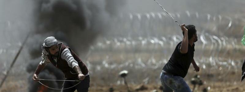 Gazastreifen - Foto: Palästinensische Demonstranten schleudern Steine inRichtung israelischerSoldaten hinter dem Grenzzaun. Foto:Khalil Hamra/AP