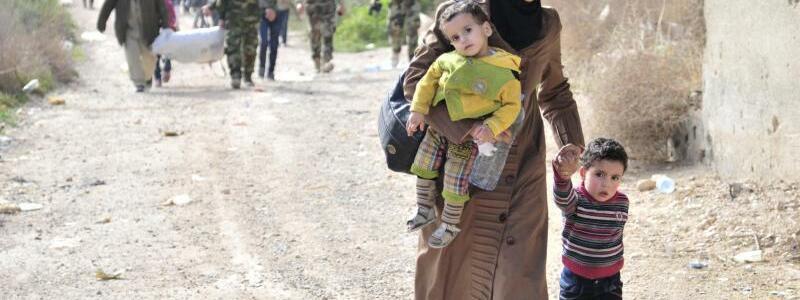 Flucht - Foto: Eine Mutter verlässt mit ihren Kindern das umkämpfte Rebellengebiet. Foto:Sana/AP