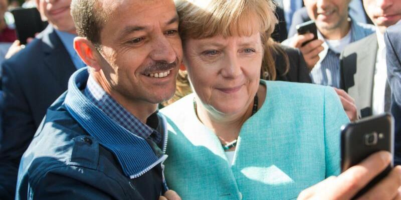 Selfie mit Merkel - Foto: Angela Merkel posiert bei einem Besuch in einer Erstaufnahmeeinrichtung in Berlin im September 2015 zusammen mit einem Flüchtling für ein Selfie. Für die Kanzlerin Merkel entwickelt sich der Konflikt um den richtigen Weg in der Migrationspolitik zum Hochr
