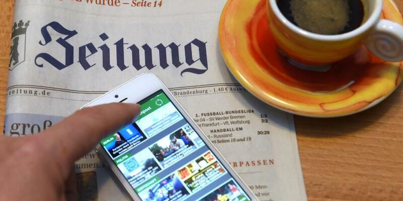 Tageszeitung und Smartphone - Foto: Jens Kalaene