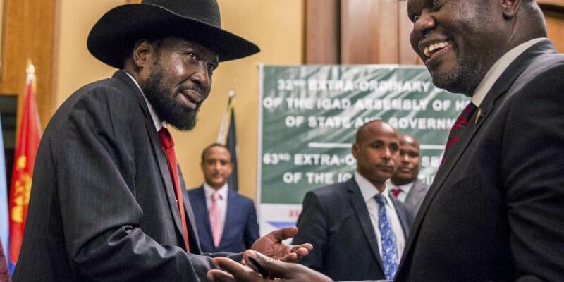 Salva Kiir und Riek Machar - Foto: Salva Kiir (l), Präsident des Südsudan, und Riek Machar, Oppositionsführer, geben sich die Hand. Foto:Mulugeta Ayene/AP/Archiv