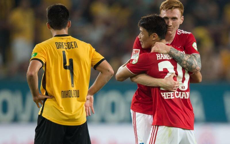 HSV-Jubel - Foto: HSV-Torschütze Hee Chan Hwang (M) jubelt nach dem Spiel mit HDavid Bates (r) neben dem frustriertem Jannis Nikolaou von Dynamo Dresden. Foto:Sebastian Kahnert