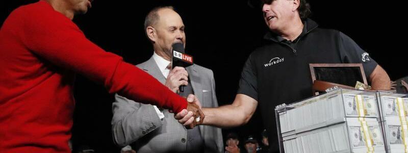 «The Match» - Foto: Neben einem Haufen Banknoten reicht Sieger Phil Mickelson (r) Tiger Woods (l) die Hand. Foto:John Locher/AP