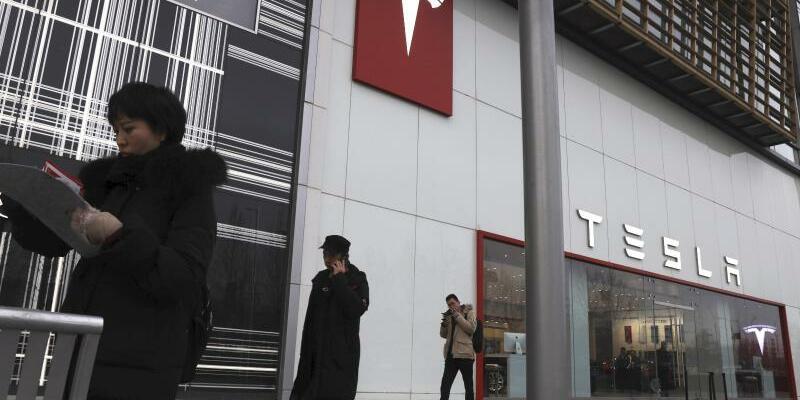 Tesla - Foto: Fußgänger gehen an einer Tesla-Filiale in Peking vorbei. Foto:Ng Han Guan/AP/dpa