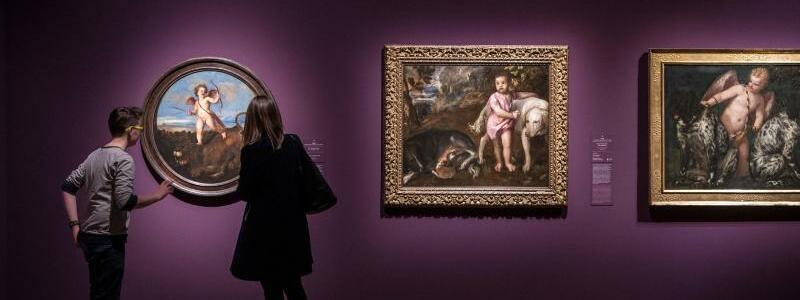 Tizian-Ausstellung im Frankfurter Städel - Foto: Eine Frau und ein junger Mann stehen vor dem Tizian-Werk Der Triumph der Liebe in der Ausstellung Tizian und die Renaissance in Venedig im Städel. Foto: