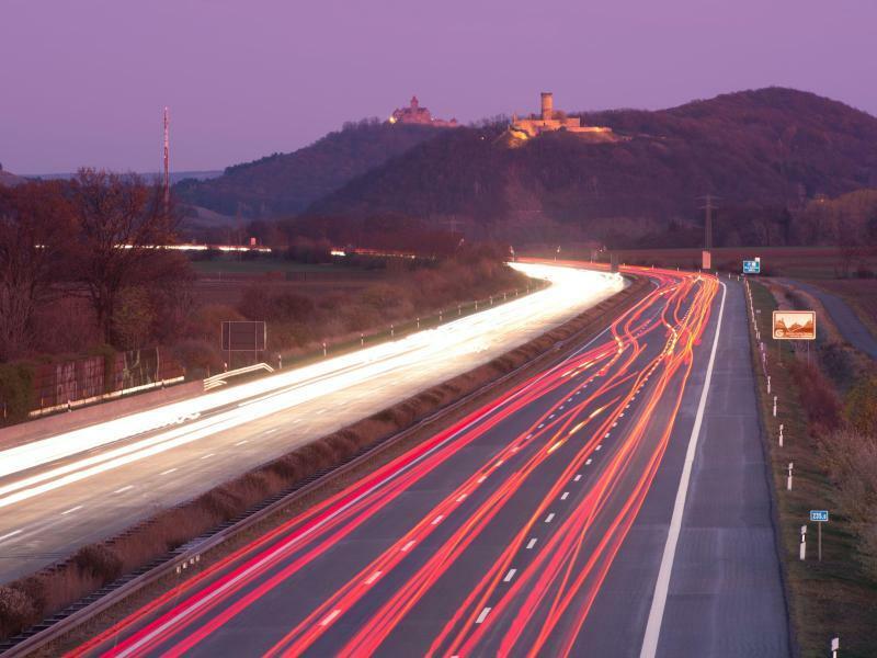 Lichtspiel - Foto: Autos fahren auf der Autobahn vor dem Burgenensemble der Drei Gleichen entlang und hinterlassen dabei Lichtstreifen. Foto:Sebastian Kahnert