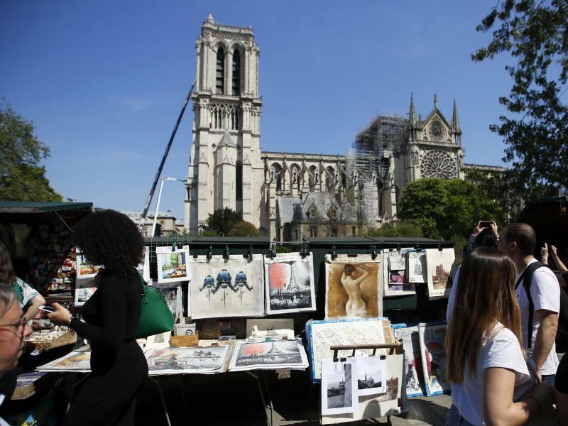 Nach dem Brand - Foto: Menschen gehen an einem Verkaufsstand am Seine-Ufer in Paris entlang, während im Hintergrund die beschädigte Kathedrale Notre-Dame zu sehen ist, neben der ein Kran steht. Nach dem Brand begann der Abtransport großer Ölbilder. Außerdem soll über dem Bauwer