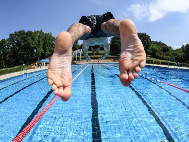 Kopfüber ins Vergnügen - Foto: Ein Schwimmer stößt sich bei sommerlichen Temperaturen von einem Startblock eines Schwimmbads in Darmstadt. Die hessischenSchwimmbäder sind in die Saison gestartet. Foto:Arne Dedert