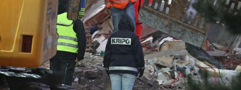 Unglück im Allgäu - Foto: Eine Mitarbeiterin der Kriminalpolizei steht in den Trümmern eines zerstörten Hauses. Am Morgen wurde dort die Leiche eines Mädchens gefunden. Foto:Karl-Josef Hildenbrand