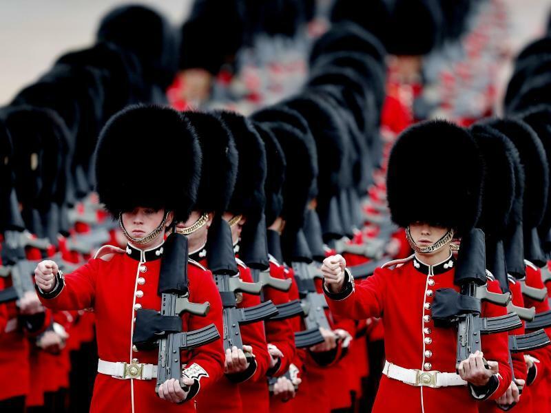 Im Gleichschritt - Foto: Mit den typischen Bärenfellmützen und geschulterten Gewehren marschieren britische Soldaten bei der Parade zum 93. Geburtstag der Queen in London auf. Foto:Frank Augstein
