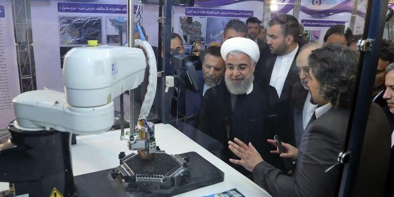 Nationaler Atomtag im Iran - Foto: Irans Präsident Hassan Ruhani (M.) lässt sich neue Entwicklungen in der Atomenergie im Rahmen des «NationalenAtomtags» erklären. Foto:Iranian Presidency Office/AP