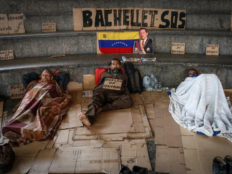 Fahnenappell - Foto: Mit einer venezolanischen Flagge, einem Porträt des ex-Staatschefs Hugo Chavez und einem Plakat an UN-Menschenrechtskommissarin Bachelet, der gerade im Lande zu Besuch ist, machen diese drei Männer auf ihren Hungerstreik aufmerksam. Foto:Daniel Hernandez