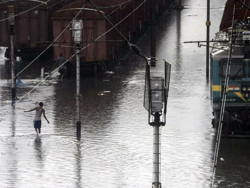 Monsun - Foto: Starke Regenfälle haben im Westen Indiens für zum Teil schwere Überschwemmungen gesorgt. Alleine in der Finanzmetropole Mumbai gab es 21 Tote. Foto:Rajanish Kakade, AP