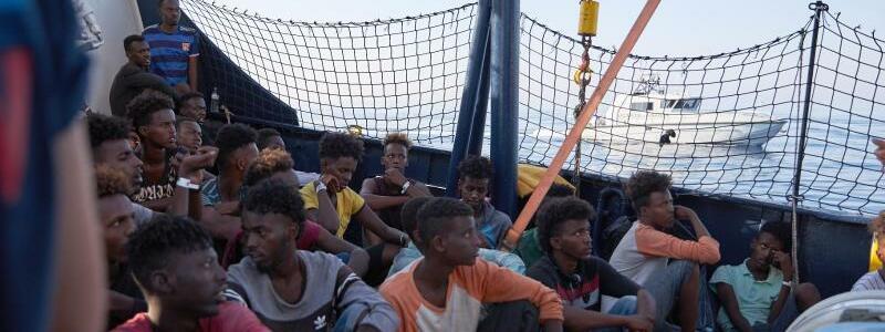 «Alan Kurdi» - Foto: Wohin?Flüchtlinge an Bord des Seenotrettungsschiffs «Alan Kurdi», während ein Boot der italienischen Guardia di Finanza vorbei fährt. Foto:Fabian Heinz/Sea-Eye