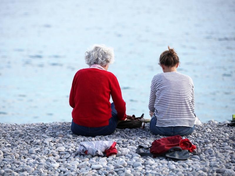Alte und junge Frau sitzen am Strand - Foto: über dts Nachrichtenagentur