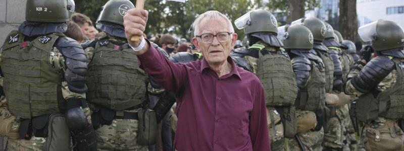 Proteste in Belarus - Foto: Ein ?lterer Demonstrant steht bei einem Protest der belarussischen Opposition gegen die Ergebnisse der Pr?sidentenwahl vor einer Gruppe von Polizisten und h?lt ein Schild mit der Aufschrift ?Wir werden nicht vergessen, wir werden nicht verzeihen? in der H